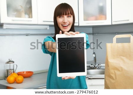 selective focus. young housewife uses a tablet computer in the kitchen. woman following recipe cooking vegetables on digital tablet. online food shopping - stock photo
