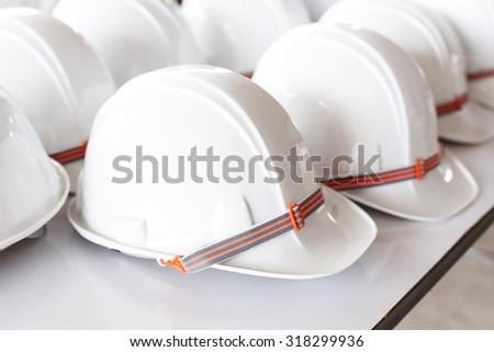 Selective white construction helmets on white table.  - stock photo