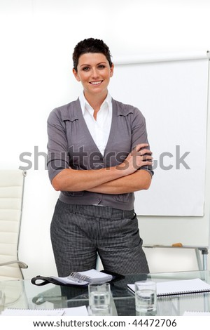 Self-assured female executive with folded arms in front of a board - stock photo