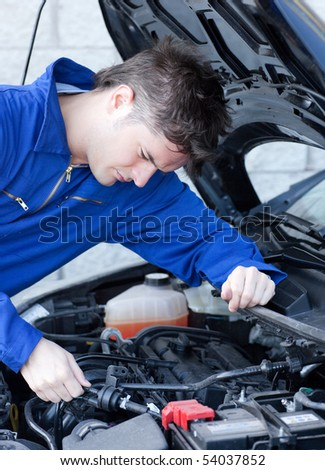 Self-assured man repairing a car in a garage - stock photo