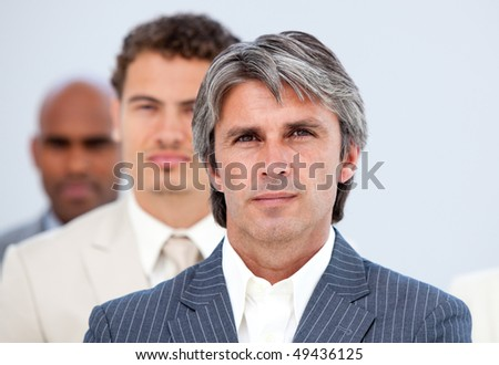 Self-assured manager and his team looking at the camera in a company