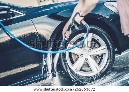 Self Car Washing. Cleaning Wheels Using High Pressure Water.  - stock photo