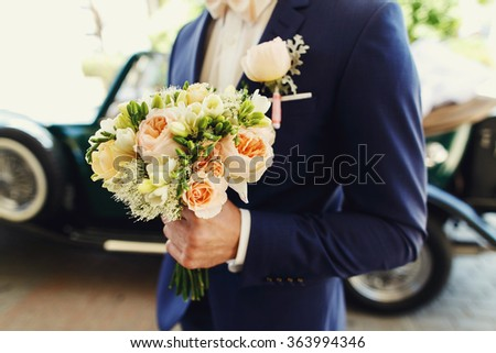 Self confident groom in a blue suit with a luxury bouquet of flowers standing near the wedding car on bright sunny day. - stock photo