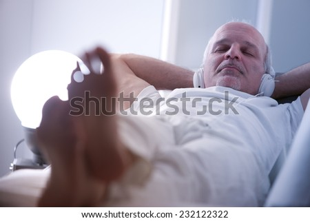 self-confident mature man relaxing on a sofa in a white living room - stock photo