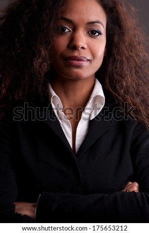 Self confident serious  businesswoman arms akimbo - stock photo