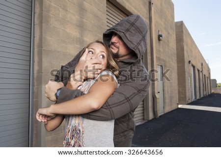 SELF DEFENSE | A young woman sees a suspicious person walking behind her and plans to defend herself against a male attacker in an alley.    - stock photo