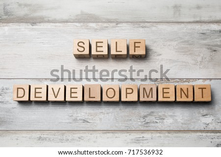 self development text on wooden cubes on wooden background