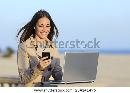 Self employed woman working outdoors on the phone with a beach in the background - stock photo