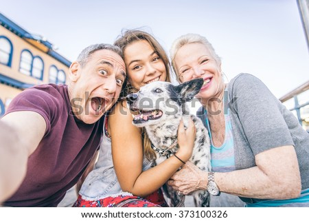 Self portrait of happy family with dog having fun outdoors - Grandparents and nephew taking a selfie - stock photo