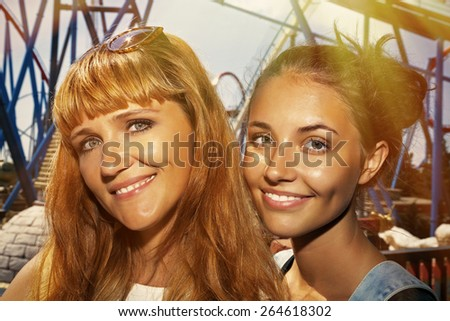 Self-portrait of two girls at an amusement park. - stock photo