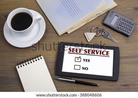 Self Service. Text on tablet device on a wooden table - stock photo
