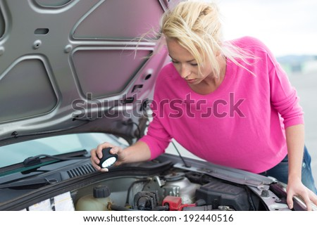 Self-sufficient confident modern young woman inspecting broken car engine with a flashlight in her hand.  - stock photo