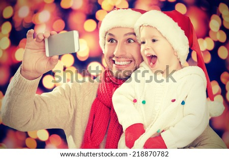 selfe  in Christmas. happy family dad playing with daughter and photographed on  mobile phone - stock photo