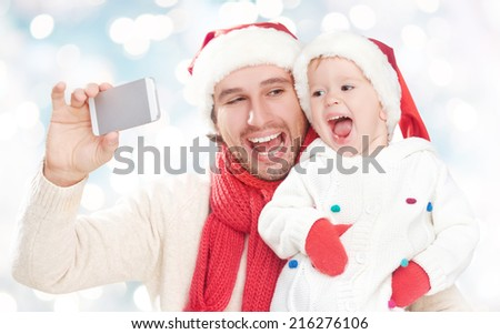 selfe  in winter. happy family father dad playing with baby daughter and photographed on a mobile phone - stock photo