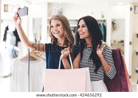 Selfie after successful shopping. Two beautiful women with shopping bags making selfie while standing at the clothing store - stock photo