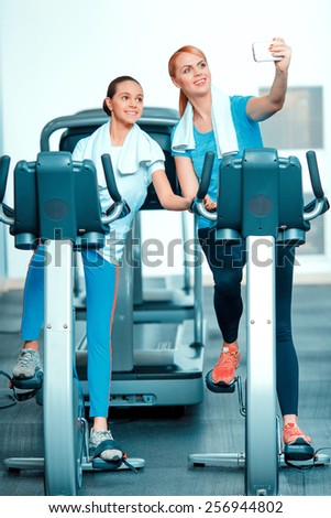 Selfie. Beautiful mature woman bonding her teenage daughter in sports clothing after workout on exercise bicycle in the gym and doing selfie on her smartphone
