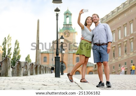 Selfie couple taking pictures at Stockholm cathedral and royal palace in Gamla Stan (Old Town) in the capital of Sweden. Tourists people taking travel photos with smartphone on summer holidays.