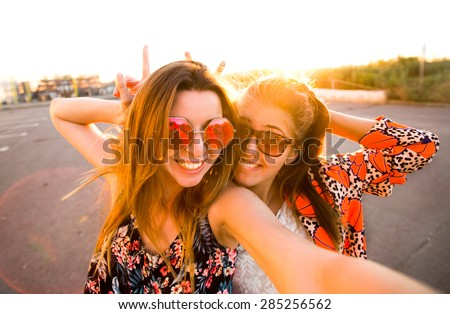Selfie fun girls taking picture at cool sunset.Summer holidays, girls at smartphone camera taking self-portrait on their travel vacations.Best friends girls make picture at sunset,camera selfie pic - stock photo