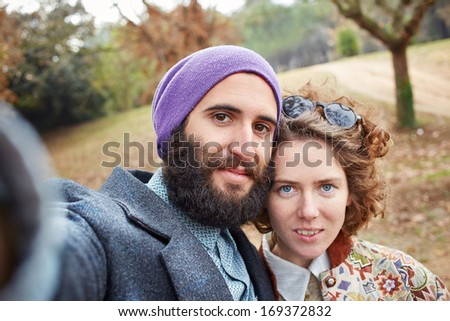 Selfie of a young hipster couple outdoors - stock photo
