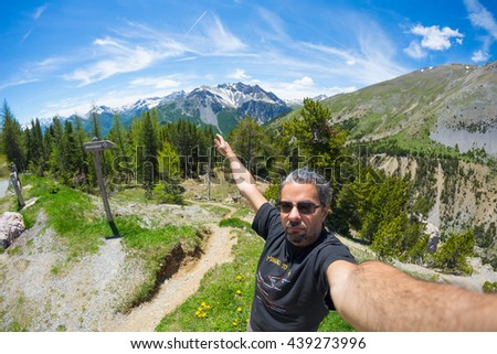 Selfie of adult hiker on top of trail crossing high altitude conifer woodland with snowcapped mountain range in background and moody blue sky. Scenic fisheye distortion. - stock photo