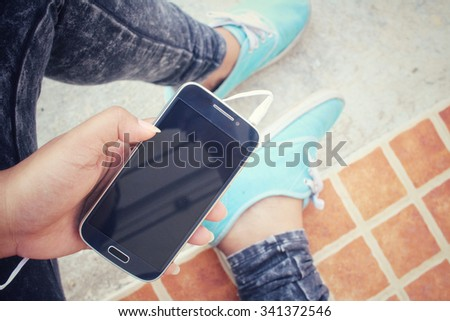 Selfie of sneakers with earphone and smart phone