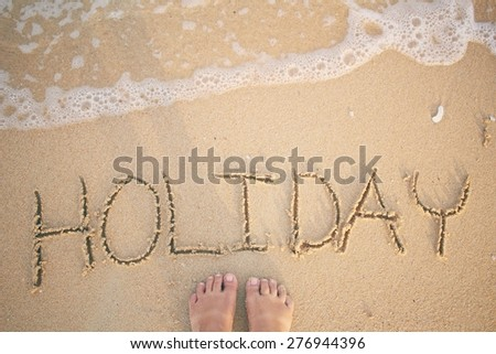 Selfie of word holiday written in sand on beach  - stock photo