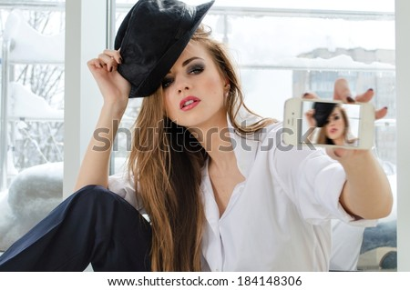 Selfie or selfy portrait: Beautiful young woman taking picture of herself on mobile  - stock photo