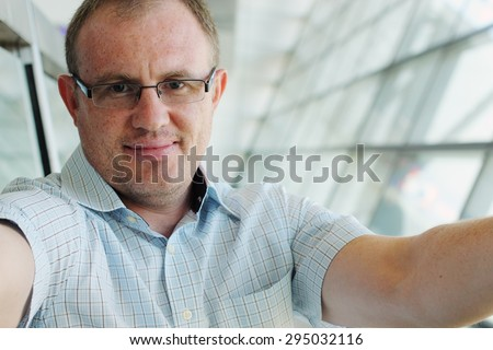 Selfie portrait of a handsome 35 years old man smiling indoor