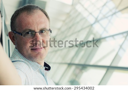 Selfie portrait of a handsome 35 years old man smiling indoor - stock photo