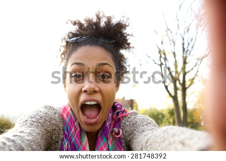 Selfie portrait of a happy young woman shouting - stock photo