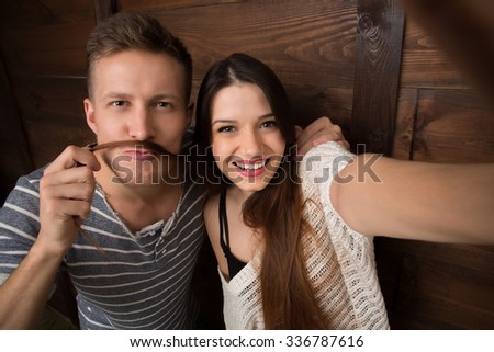 Selfie project. Young couple posing for mobile phone's camera. Handsome man and woman mankig selfies isolated on wooden background. - stock photo
