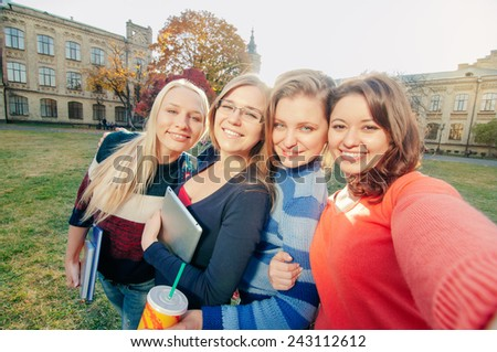 Selfie! Smiling female students taking pictures in the campus - stock photo