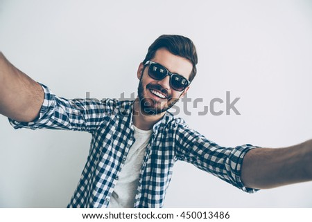 Selfie time! Studio shot of handsome young man in sunglasses making selfie and smiling   - stock photo