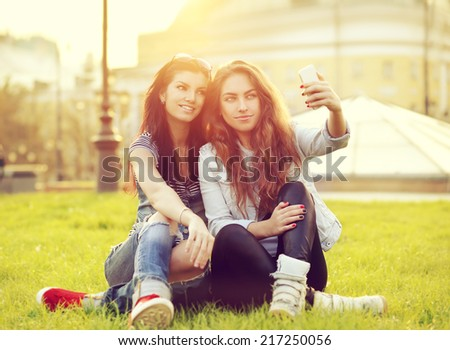 Selfie .Two cheerful friends taking photos of themselves on smart phone - stock photo
