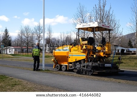 SELFOSS, ICELAND-MAY 4 :Workers operating man calling phone and asphalt paver machine and heavy machinery during repairs road under the program repairs highway road on May 4, 2016 in Selfoss, Iceland. - stock photo