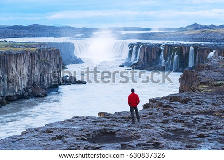 Selfoss waterfall. Guy in a red jacket looks at a cascade of water. Famous tourist attraction of Iceland. Beauty in nature