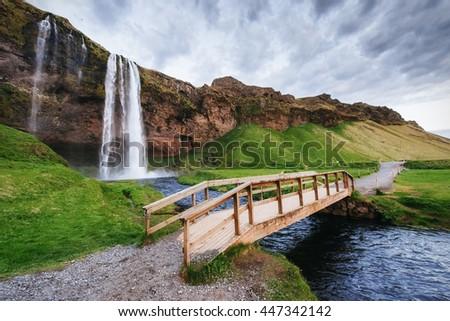 Seljalandfoss waterfall at sunset. Bridge over the river. Fantastic nature. Iceland. Europe - stock photo