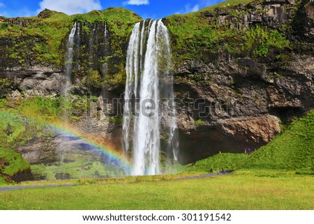 Seljalandsfoss waterfall in Iceland. Sunny day in July. Large rainbow decorates a drop of water - stock photo
