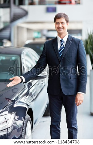Seller about a car showroom - stock photo