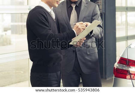 Seller or car salesman explaining the term and condition to the customer in car showroom