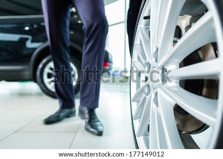 Seller or car salesman in car dealership presenting the extra decorations like sport rims of his new and used cars in the showroom - stock photo