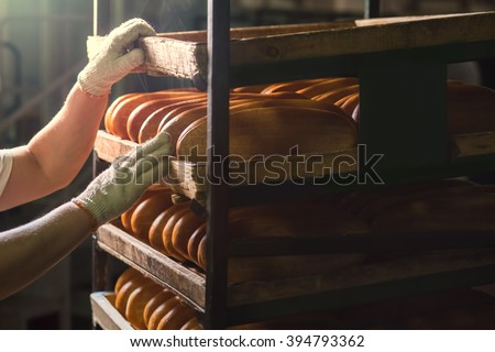 Seller puts  bread on  shelf. Fresh buns from the oven. Baking bread. Transportation of baking. Confectionery. - stock photo