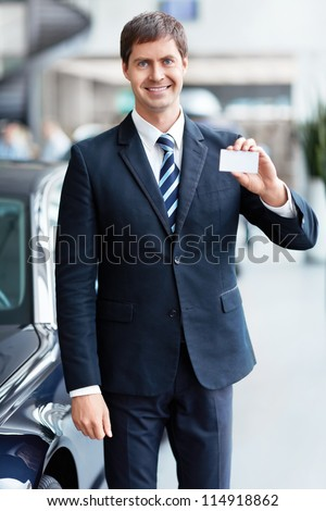 Seller with a business card in the showroom - stock photo
