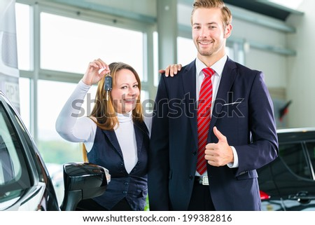Sellers or car salesman and female customer in dealership, the woman holding the key in the hand and is pleased about the purchase of the auto or new car   - stock photo