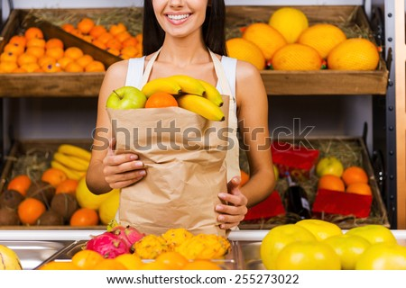 Selling health. Cropped image of beautiful young woman in apron holding paper shopping bag with fruits and smiling while standing in grocery store with variety of fruits in the background  - stock photo