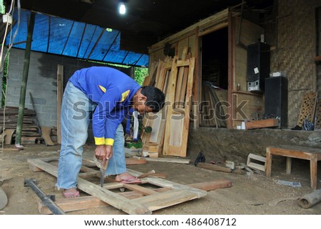 SELO, INDONESIA - APRIL 17: An unidentified old village man is preparing  door frame in the village near Selo in Java, Indonesia on Apr 17, 2013