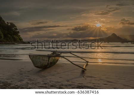 Selong Belanak beach, South Lombok, Indonesia - April 21, 2017 : Fishing boat lonely on the beach during sunset