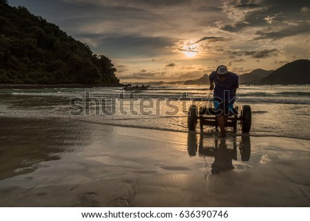 Selong Belanak beach, South Lombok, Indonesia - April 21, 2017 : Pulling a boat cart back on shore