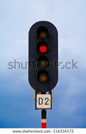 Semaphore, traffic light on train station shot against blue, clouded sky. - stock photo