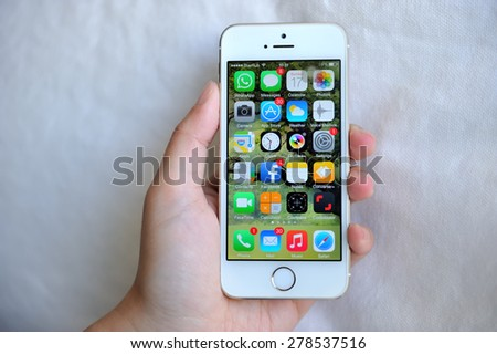 SEMBAWANG, SINGAPORE - MAY 17, 2015: Woman holding white Apple iPhone 5S. Social media are trending and both business as consumer are using it for information sharing and networking. - stock photo